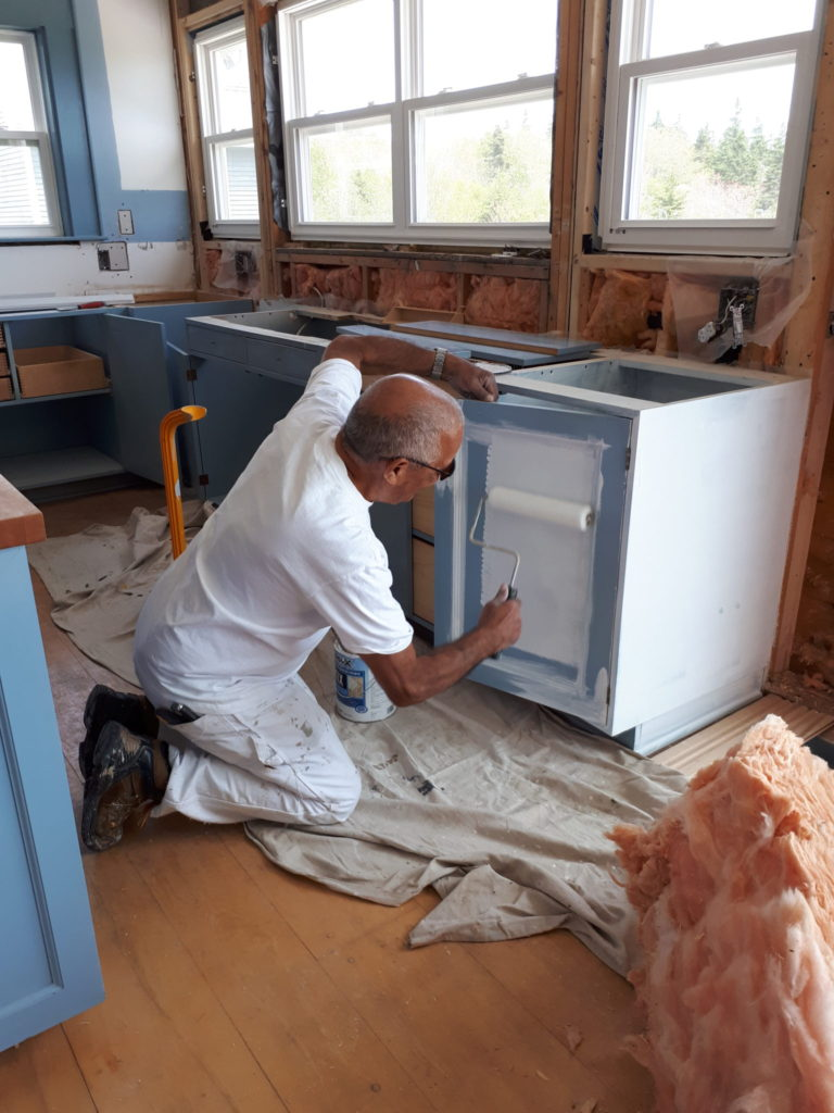 painter priming cabinets